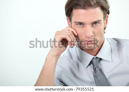Young businessman with hand to face - stock photo