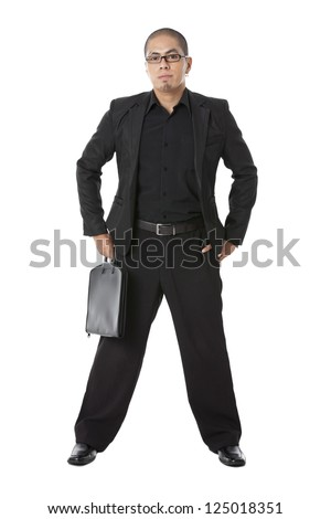 Young businessman with hands on his hips as he hold his briefcase over white background - stock photo