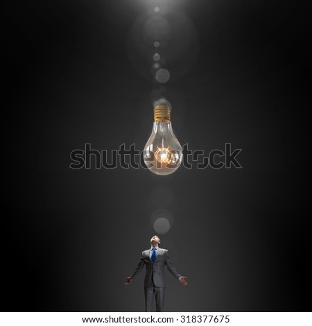 Young businessman with hands spread looking at light bulb above his head