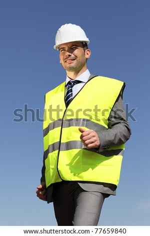 young businessman with hardhat and blue sky - stock photo