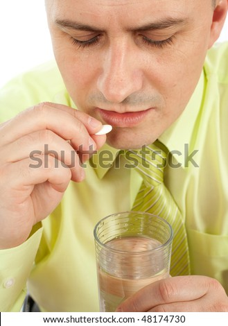 Young businessman with headache taking a pill - stock photo