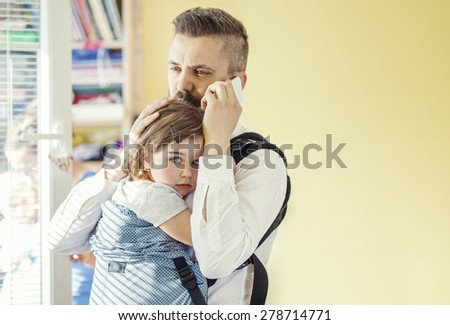 Young businessman with his daughter talking on a phone - stock photo