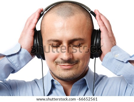 Young businessman with his eyes closed listening music on headphones - stock photo