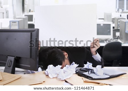 Young businessman with his face down while holding a white copy space at his office - stock photo
