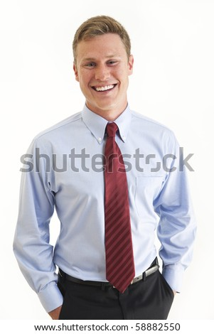 Young businessman with his hands in his pockets looking at the camera and smiling - stock photo