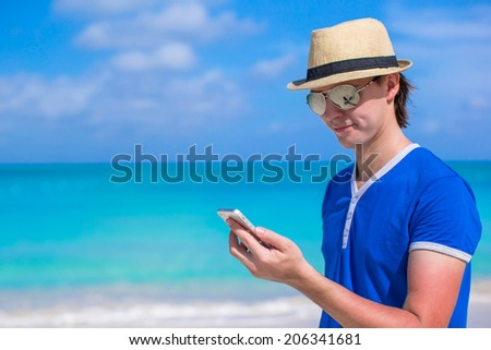 Young businessman with his phone on beach vacation - stock photo