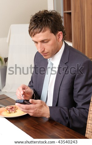 Young businessman with his smartphone (cell) at the breakfast - stock photo