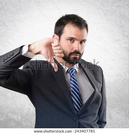 Young businessman with his thumb down over textured background - stock photo