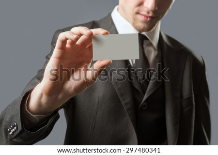 Young businessman with holding up his blank white card card to show his credentials and qualification. Isolated on gray. - stock photo