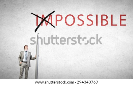 Young businessman with huge pencil changing word impossible - stock photo