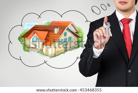 Young businessman with keys in hand thinking about real estate on hrey background. Mortgage concept
