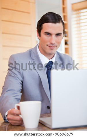 Young businessman with laptop and tea - stock photo