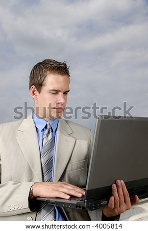 Young businessman with laptop in his hands outdoor.