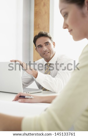 Young businessman with laptop looking at female colleague during meeting in office - stock photo