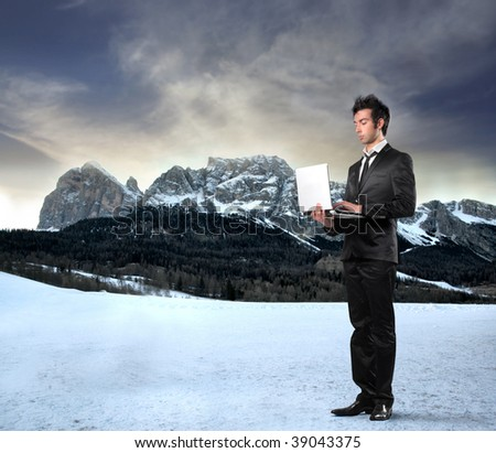 young businessman with laptop on a mountains landscape background - stock photo