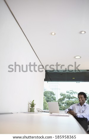 Young businessman with laptop using cell phone at desk (low angle view) - stock photo