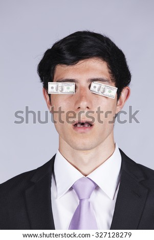Young businessman with little dollar bills covering his eyes - stock photo