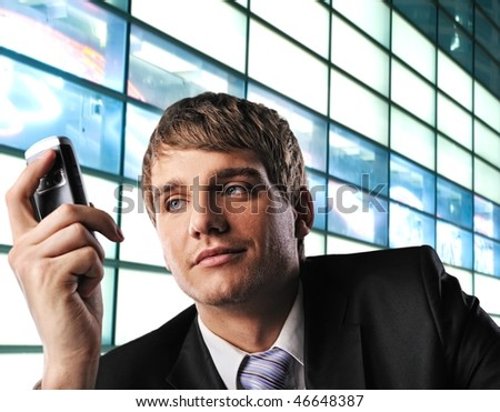 Young businessman with mobile phone over abstract background - stock photo