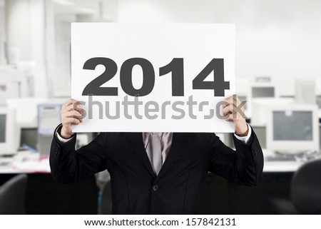 Young businessman with New Year 2014 at office - stock photo