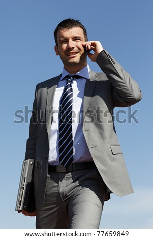 young businessman with phone and blue sky