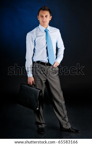 young businessman with portfolio. Against a dark background - stock photo