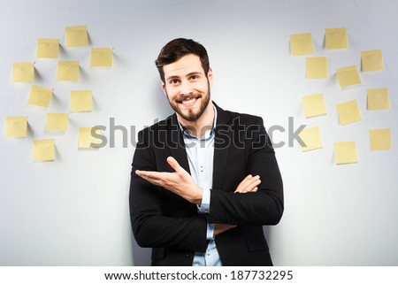 young businessman with postit reminder notes on the background - stock photo