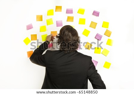 young businessman with postit reminder notes on the background