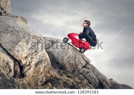 young businessman with red car climbs the rocks