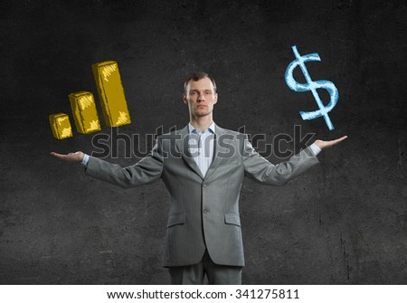 Young businessman with spread arms holding financial growth symbols