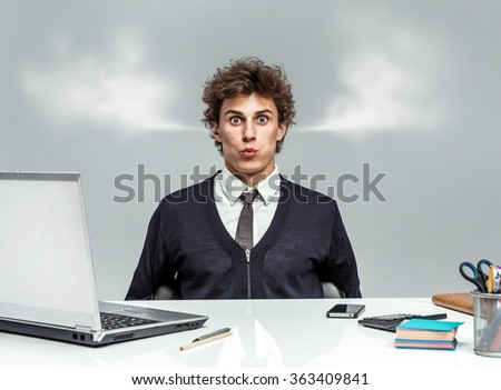 Young businessman with steam from his ears / businessman at the workplace looking at camera on grey background. Depression and crisis concept - stock photo