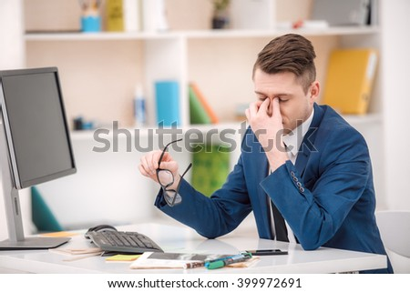 Young businessman with suit working in office. Businessman using computer and having headache. Office interior with bookcase