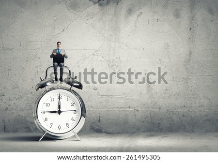 Young businessman with suitcase sitting on alarm clock - stock photo