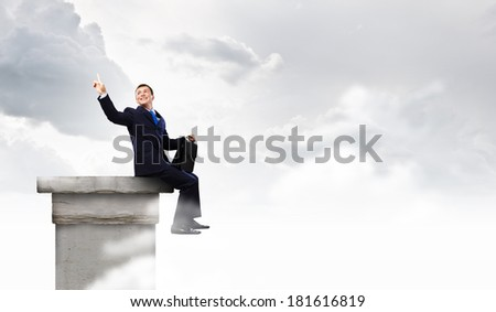 Young businessman with suitcase sitting on roof of building