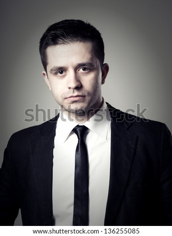 Young businessman with surprise expression on his face on a gray background - stock photo