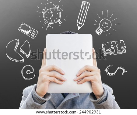 young businessman with tablet in front of his face surrounded of sketches symbols on the wall - stock photo