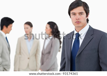 Young businessman with talking associates behind him against a white background - stock photo