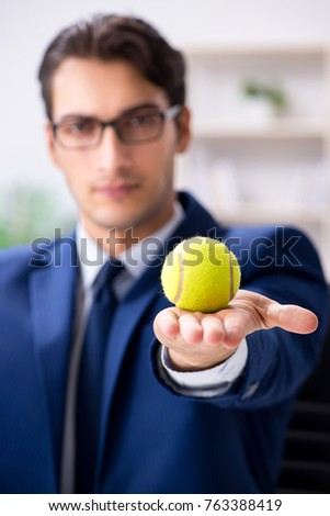 Young businessman with tennis ball working in office