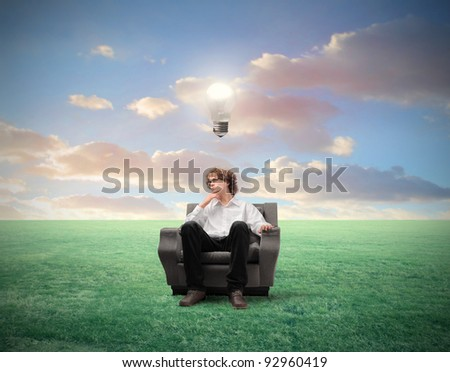 Young businessman with thoughtful expression sitting on an armchair on a green meadow and light bulb over his head - stock photo