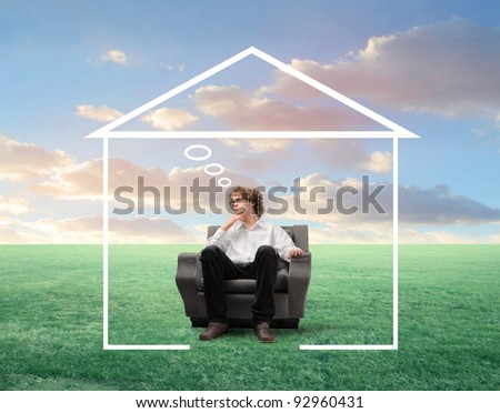 Young businessman with thoughtful expression sitting on an armchair surrounded by the shape of a house - stock photo