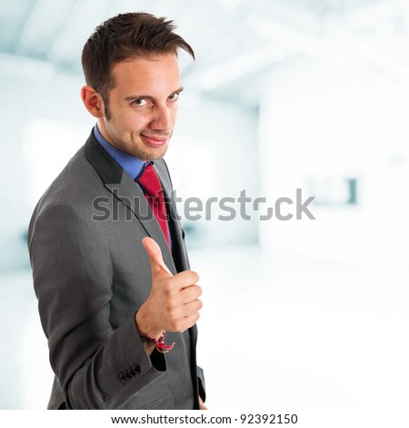 Young businessman with thumbs up - stock photo