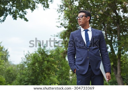 Young businessman with touchpad standing in park - stock photo