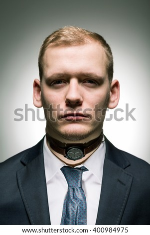 Young businessman with watch on his neck as a prisoner of passing time