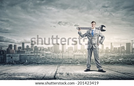 Young businessman with wrench against city background - stock photo