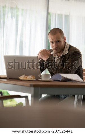 Young businessman working at cafe using laptop