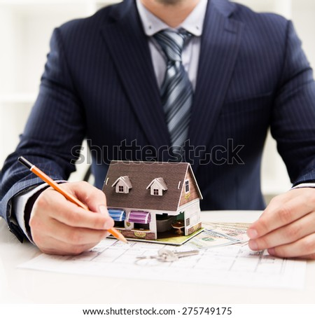 Young businessman working at house costing estimate and design. Male real estate agent sitting at the desk with blueprint, pencil and residence model.  - stock photo