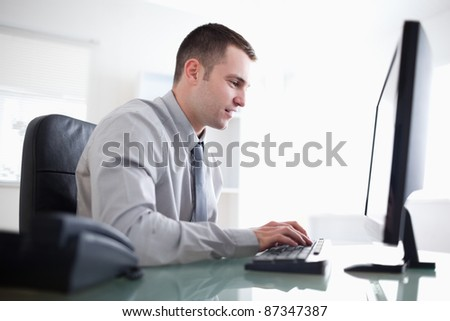 Young businessman working concentrated on his computer - stock photo