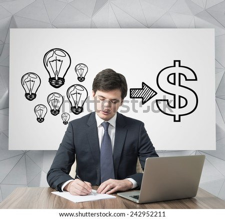 young businessman working in office and money ideas on poster - stock photo