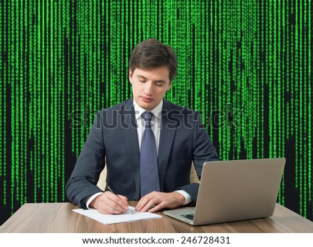 young businessman working in office on matrix background - stock photo