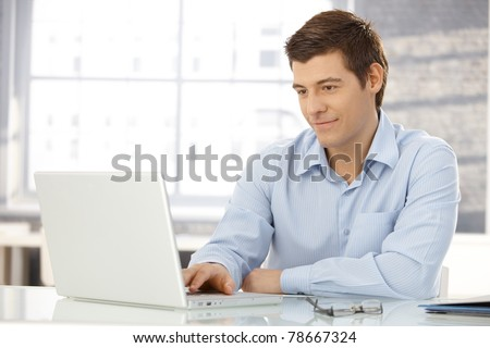 Young businessman working in office, sitting at desk, looking at laptop computer screen, smiling.? - stock photo