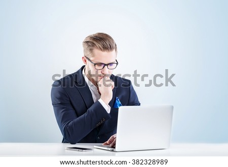 Young businessman working in office, with a serious face working for laptop - stock photo